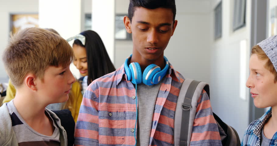 Smiling students standing with notebook and digital tablet in corridor at school | Shutterstock HD Video #26076311