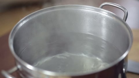 Detail of boiling water on saucepan, young woman preparing meal at the kitchen table.