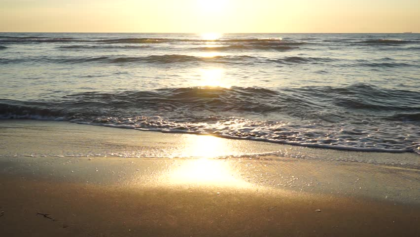 Sunset at the Adriatic Sea of Albania close to Durres at a low angle on a quiet April evening. Flat and wet sand is reflecting the golden light falling from the sun. Slow waves licking the shore.
