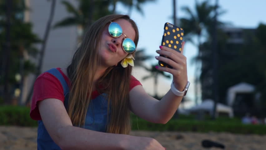 Happy Teen Girl Poses For Fun Selfies On The Beach, Resort With Palm Trees In Background, She Looks At The Photo After