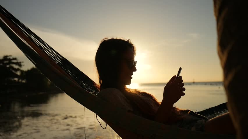 Young Girl with Smartphone in Hammock Silhuette Against Beautiful Sunset at the Beach. Koh Phangan, Thailand. HD Slowmotion. 1920x1080