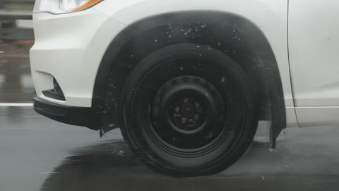 Slow motion drive. Passing vehicle. Detail of tire with droplets of water. Shot through rainy passenger window.