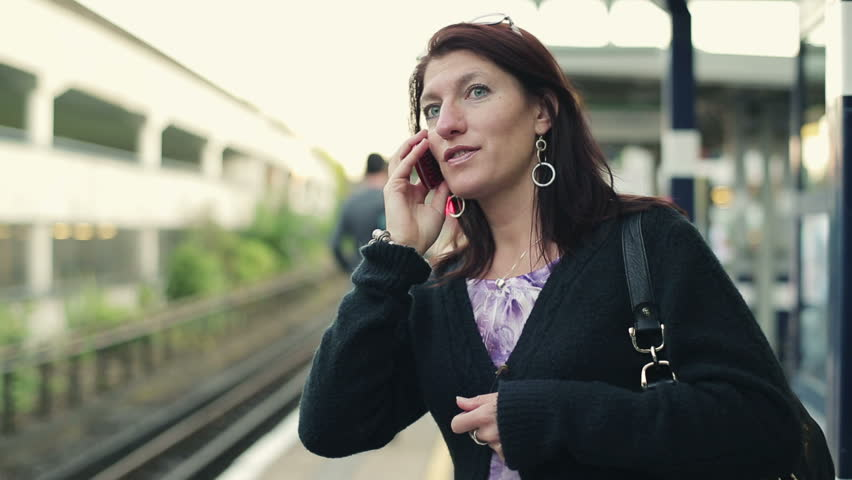 Woman talking on cellphone on train station, steadicam shot