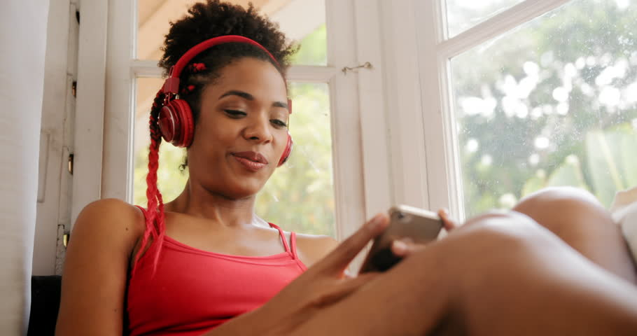Black girl lying on couch and singing song, young african american woman relaxing. Happy latina sitting on sofa and listening to music. Hispanic people and lifestyle. Leisure and relaxation at home