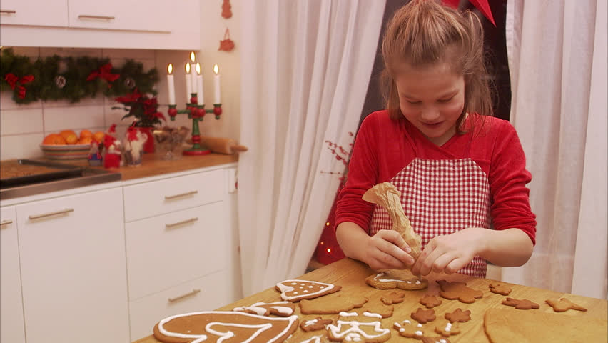 a young girl decorating gingerbread biscuits