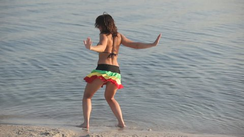 Young beautiful woman dancing in the water at summer