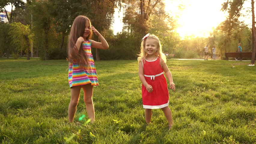 Two sisters holding hands circling on the lawn in the city park outdoors. Freedom and carefree. Happy childhood.