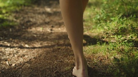 Walking woman in the forest with a white dress and bare foot