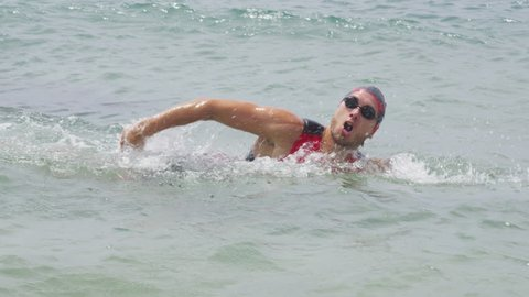 Triathlete man swimming freestyle crawl in ocean. Male triathlon swimmer swimming in professional triathlon suit training for ironman.