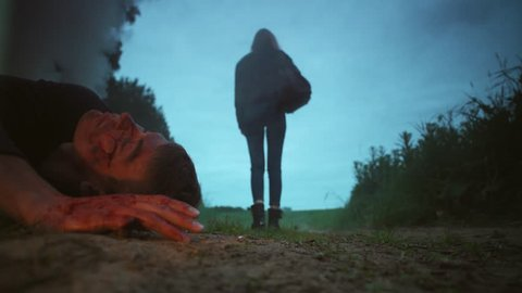 Girl n black clothes walks away into dark woods from dead man body covered in blood and dirt on side of road after car crash accident, fire smoke, summer night