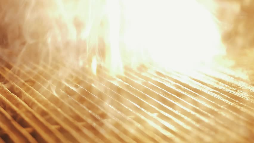 Black cooking brush apply oil on hot smoking grill, producing hight strong fire flames, close up slow motion