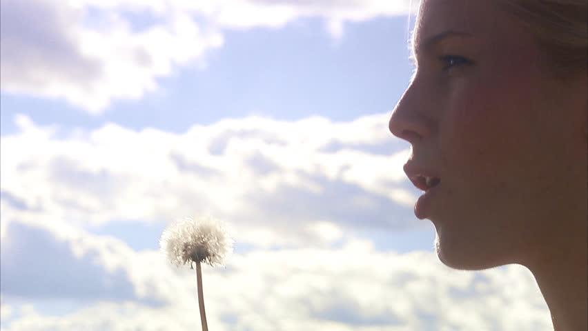 A woman blowing on a dandelion, Sweden.