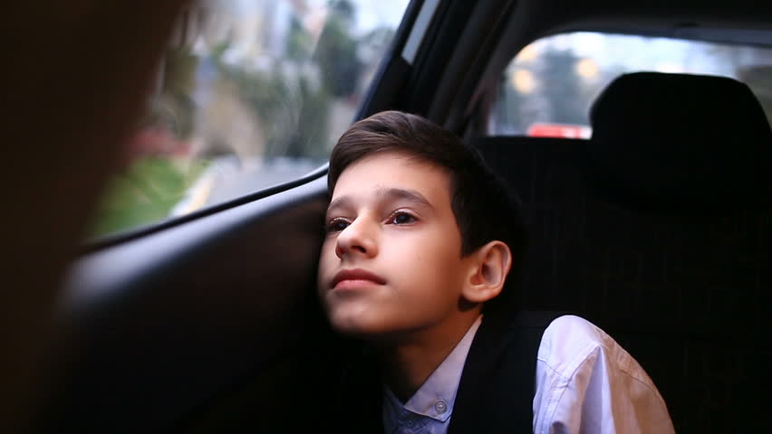 Boy teenager rides in car looking out the window. Outside the window flashed the trees and houses of the city