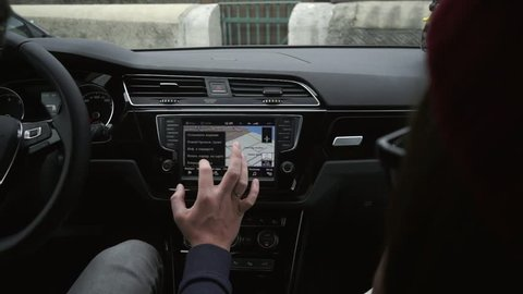 Man's hand using touch screen monitor to adjust GPS in the car