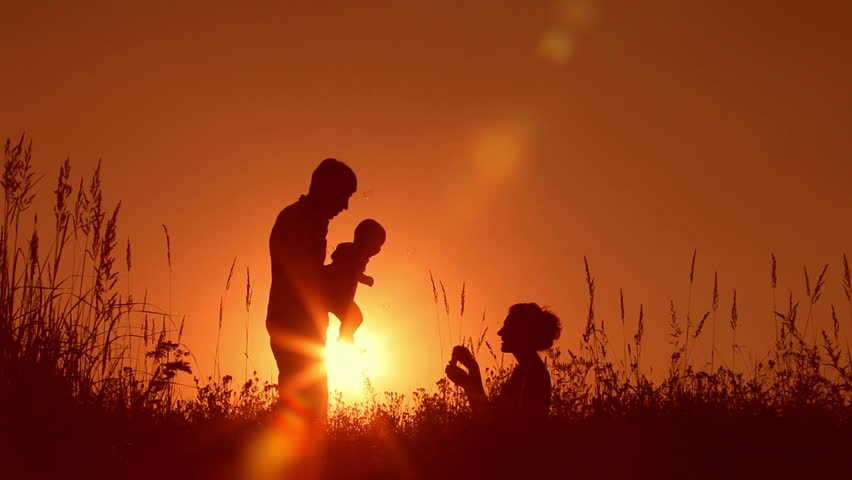 Happy family: father, mother and baby playing at sunset. Silhouettes | Shutterstock HD Video #2620769
