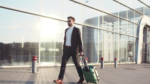 Stylish young bearded man in sunglasses exiting the airport terminal with luggage, answers the phone. Business style, traveler, modern lifestyle. Active lifestyle.