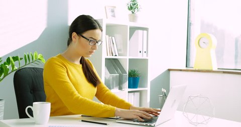 Young business woman with back pain at the office. Woman having back ache while working with laptop computer at the office