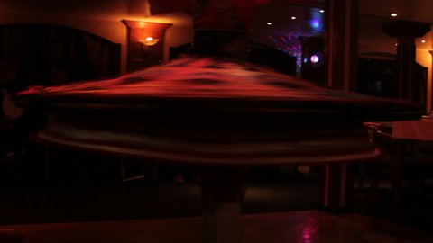 Whirling dancer performs dance in low light of darkness room