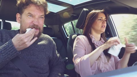 Couple driving car sneezing with strong allergy for spring with pollen in car