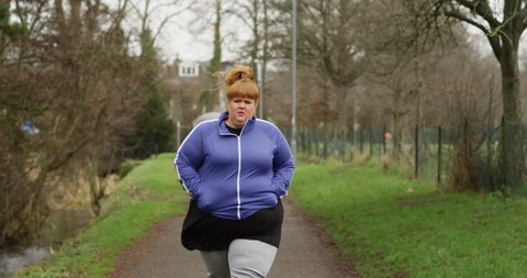 4k, Overweight woman walking on the trail in a park.