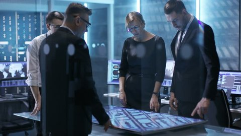 Team of Government Agents Tracking Fugitive with Help of Touchscreen Interactive Table in Big Monitoring Room Full of Computers with Animated Screens. Shot on RED EPIC-W 8K Helium Cinema Camera.