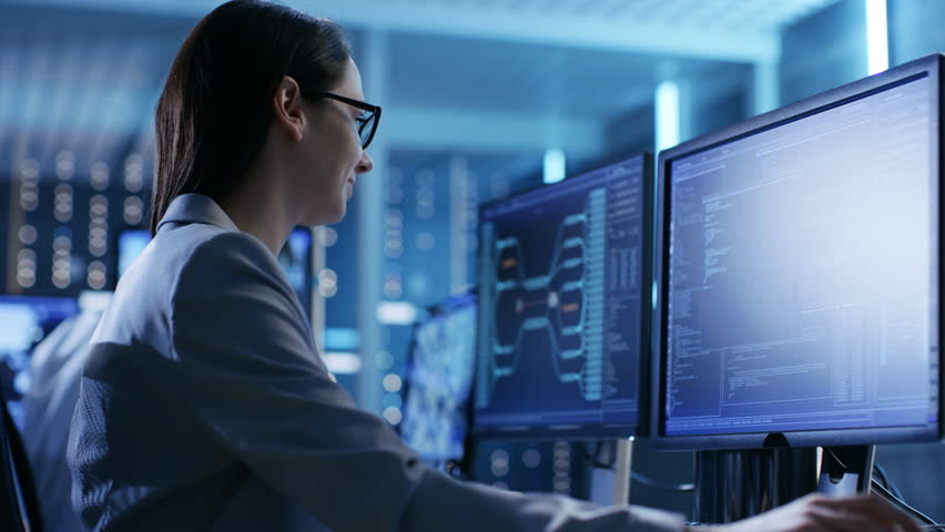 Close-up Footage of Female IT Engineer Working in Monitoring Room. She Works with Multiple Displays. In The Background Her Colleague Sitting at His Workstation.  Shot on RED EPIC-W 8K Helium Camera.