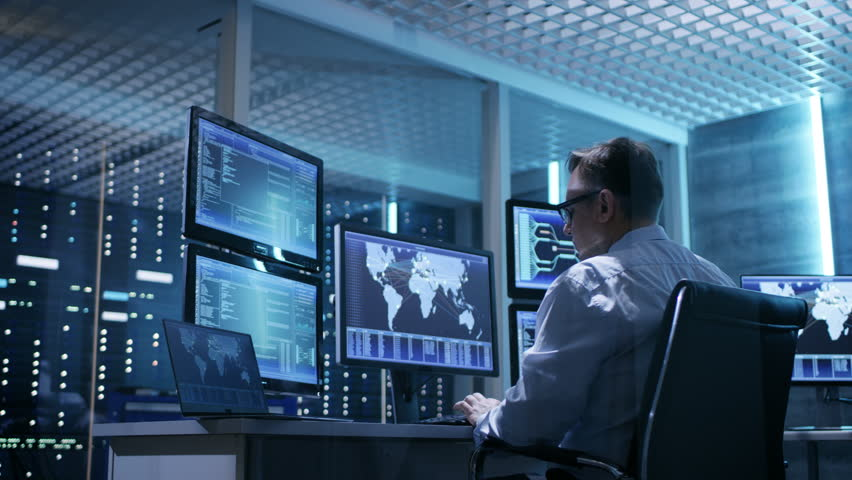 Two Technical Engineers at Sitting at Their Workplaces With Multiple Displays. They're in Monitoring Room with Servers. Shot on RED EPIC-W 8K Helium Cinema Camera. | Shutterstock HD Video #26263322