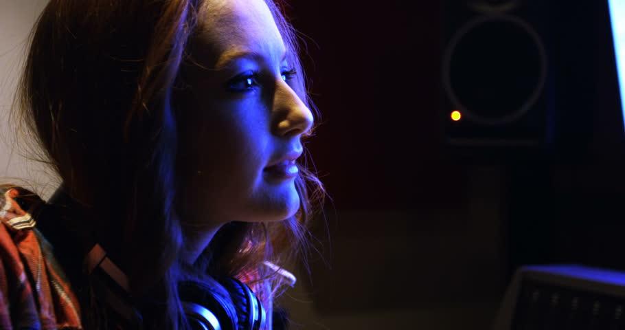Female audio engineer looking at computer screen in recording studio #26273657