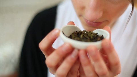 Traditional Chinese tea ceremony Gongfu - closeup of young woman taking ceramic cha he holder with dry oolong tea from table and holding it smelling green tea leaves suspiciously