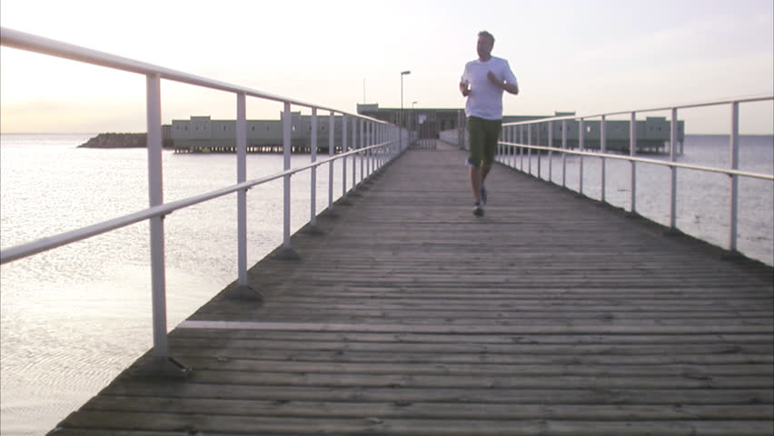 A man jogging on a boardwalk