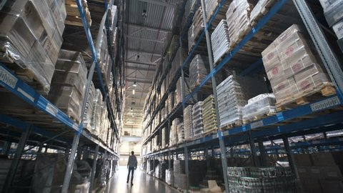 moving between palettes with ordered goods and materials at warehouse. Large warehouse logistics terminal. Shot inside Logistic Store