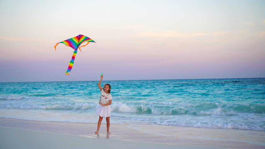 Adorable little girl with flying kite on tropical beach at sunset. Kids play on ocean shore. Child with beach toys. | Shutterstock HD Video #26284667