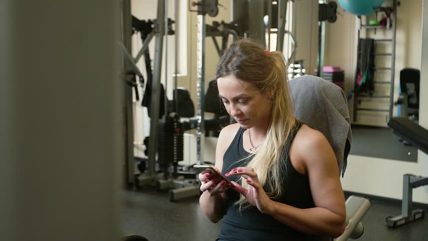 Tired after training 20s beauty sportive woman is chatting with smartphone in a machine gym | Shutterstock HD Video #26289707