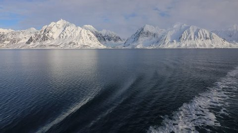 Winter coastal landscape with floating ice fragments on still dark blue sea water from the boat, Arctic, Svalbard, Norway. Land of ice. Twilight in col ocean. Sunset in fjord. Snowy nature from boat.