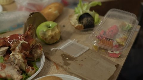Messy tables full of unhealthy food leftovers after student party in empty room