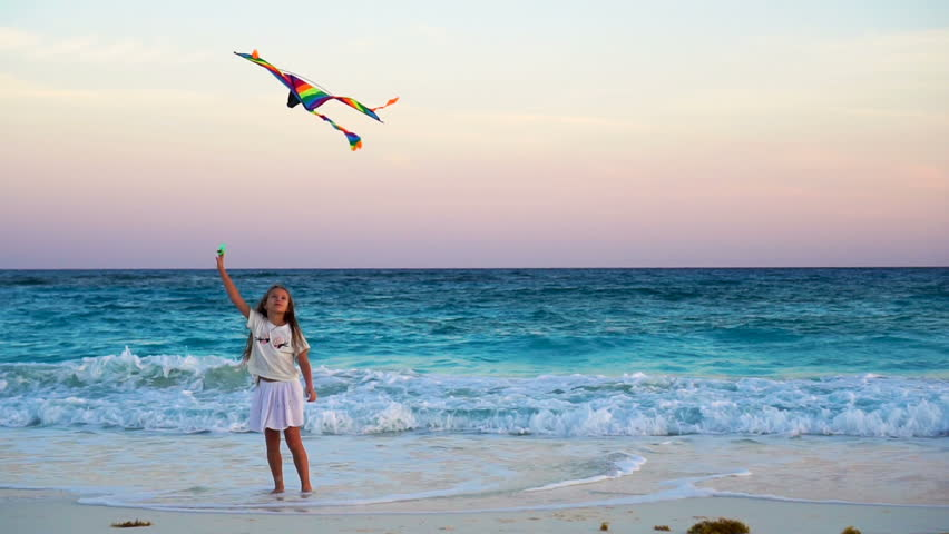 Adorable little girl with flying kite on tropical beach. Kid play on ocean shore with beautiful sunset. Slow motion. | Shutterstock HD Video #26301917