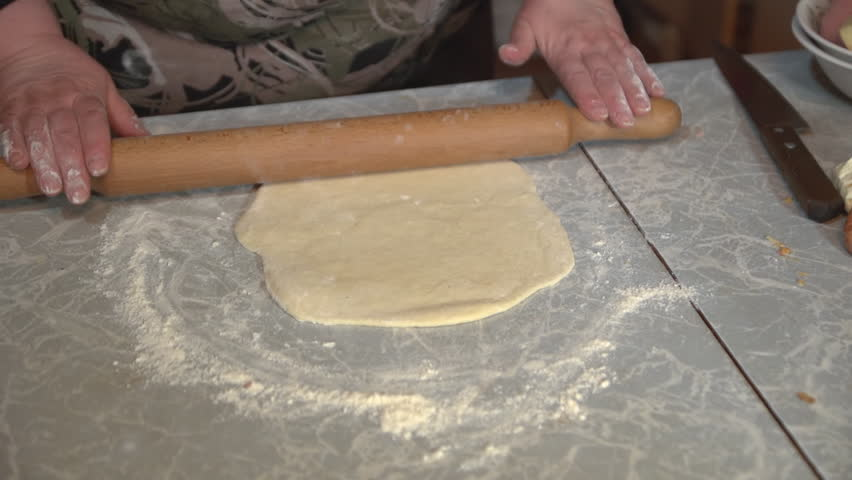 Kitchen Table Close Up a brunette woman makes a pizza dough on a light kitchen table at