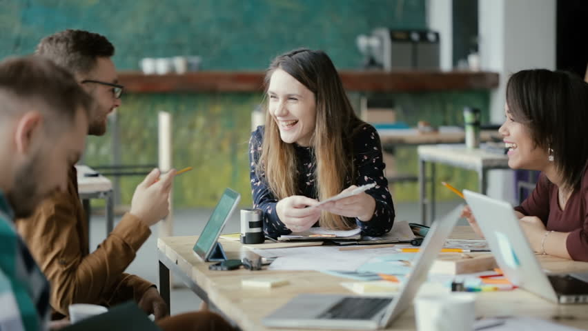 Creative business team meeting in modern office. Mixed race group of young people discussing start-up ideas, laughing. | Shutterstock HD Video #26337803