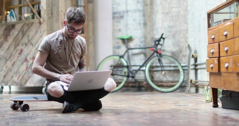 Young adult male sitting on skateboard using laptop