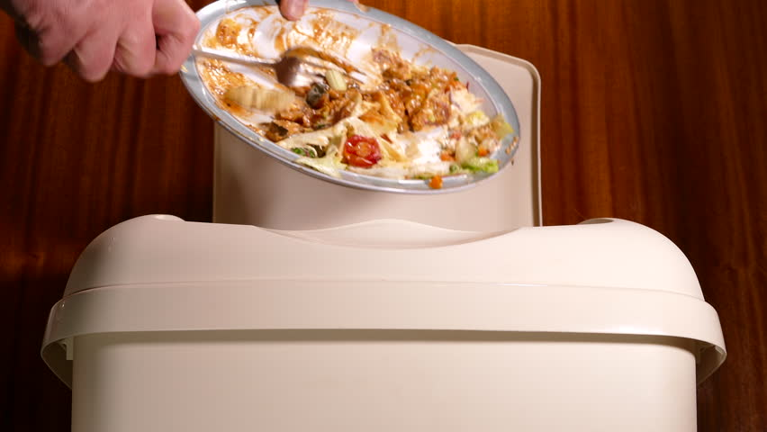 A man's hand scraping uneaten food waste from a plate into a plastic trash can/bin.
