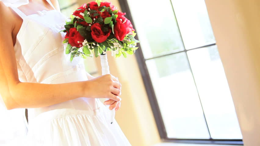 Portrait Caucasian bride with red rose posy home posing photographs