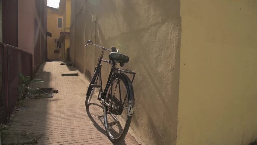 Vintage bicycle standing near the wall in a small lane