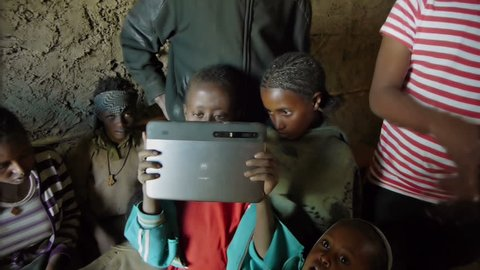 Wenchi, Ethiopia, November 2013: Young kids play with a tablet computer and take photos of their mentor in a rural place