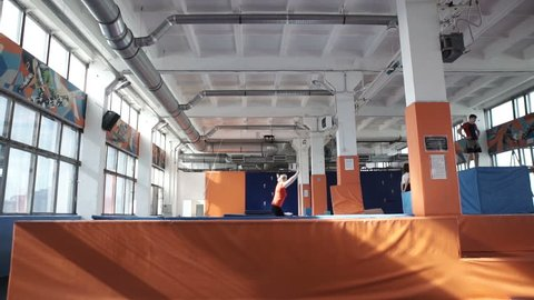 Young athetic girl is doing exercise in slow motion on a trampoline indoors