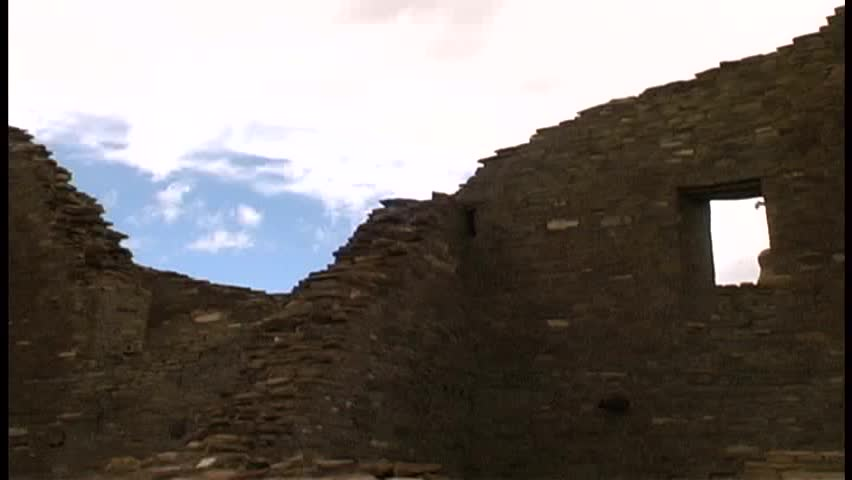 A black raven glides over the fallen walls of Pueblo Bonito in Chaco Canyon on a windy day, with blue, partly cloudy sky in the background