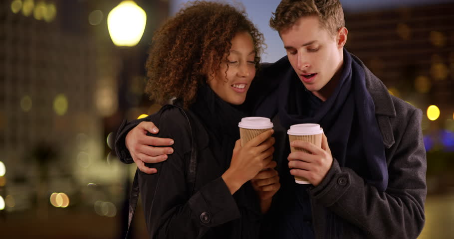 Close up portrait of couple drinking coffee at night. Stylish couple holding drinks talking with each other on city street. 4k #26416127