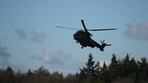 Military helicopter flying by in rough terrain.