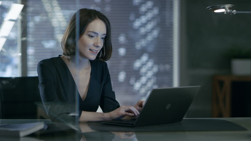 Female Executive Works on a Laptop in Her Private Office with Big City View. She's Laughing Charmingly. Her Workspace is Done in Dark Overtones. Shot on RED EPIC-W 8K Helium Cinema Camera.