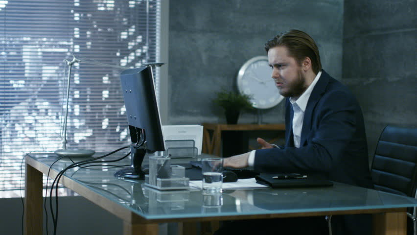 In a Private Office Businessman Loses Temper and Hits His Monitor With Keyboard, in an Act of a Rage Throws everything off the Table. Shot on RED EPIC-W 8K Helium Cinema Camera.
