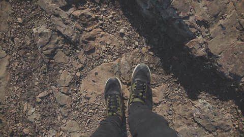 Feet over the abyss. Only legs: the tourist sits on the edge of the mountain cliff and chattering with his feet. A mountain abyss underfoot. A cold-blooded tourist sits on the edge of the abyss.